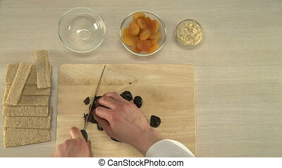 Prunes cutting for a cake - Cook cutting prunes for a...