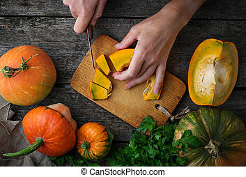 Woman cuts a pumpkin. Selective focus, top view