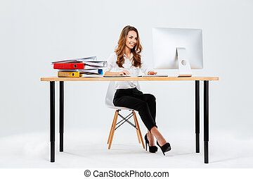 Beautiful happy businesswoman using computer while sitting at the desk