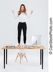 Furious young businesswoman standing on table and throwing...
