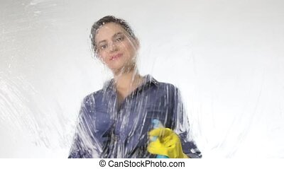 young housewife washed window with a spray, cloth and...