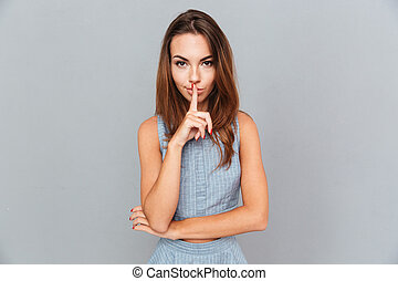Attractive young woman standing and showing silence sign