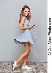 Cheerful young woman listening to music from mobile phone
