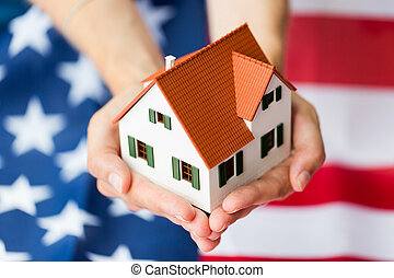 close up of hands holding house over american flag -...