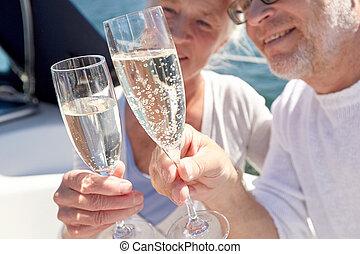 close up of senior couple with champagne on boat - sailing,...