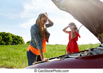 women with open hood of broken car at countryside - road...