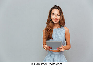 Portrait of happy lovely young woman standing and using...