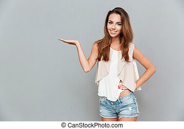 Cheerful attractive young woman standing and holding...