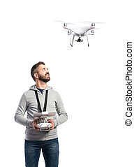 Man with flying drone. Studio shot on white background,...