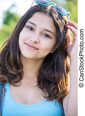 Portrait of beautiful teen girl with sunglasses on head -...