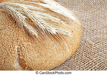 Bread and stalks of wheat on a burlap background