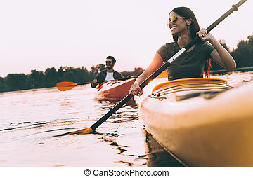 Enjoying nice time on river together. Low angle view of...