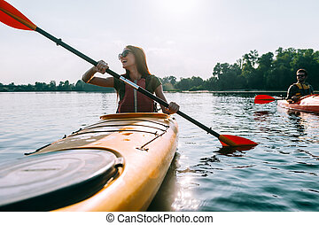 Ready for adventures. Beautiful young smiling couple kayaking on lake together