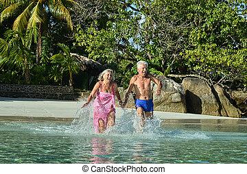 elderly couple running  on beach