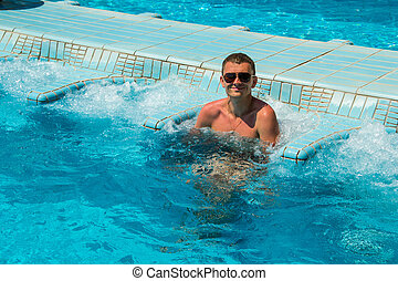 Smiling man tourist relaxing in pool jacuzzi outdoor at spa resort enjoying luxury life. Success, healthy lifestyle, body care concept.