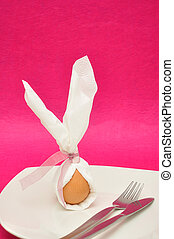 An egg in a napkin with bunny ears displayed on a plate with...