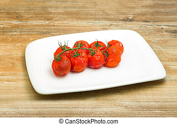 Succulent grilled cherry tomatoes ready to be served as a...