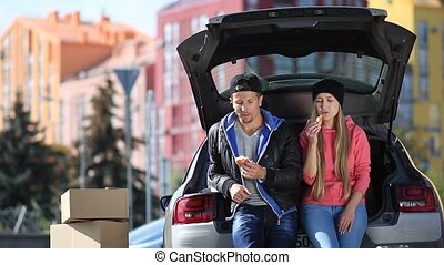 Smiling couple sitting in trunk of modern car and having a...
