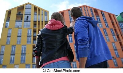 Young couple buying new apartment in modern building. Back...