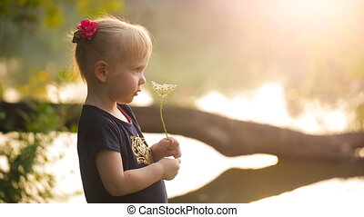 Little girl with a flower on nature at sunset