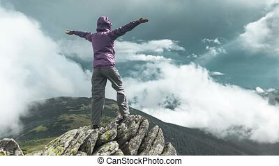 Woman on top of a mountain - Woman standing on top of a...