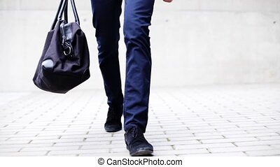young man with bag walking along city street