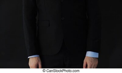 businessman in suit adjusting sleeves and tie - business,...
