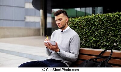 man with notebook or diary writing on city street -...