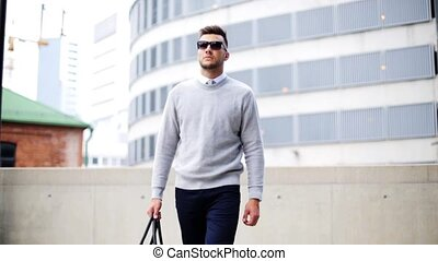 young man with sunglasses and bag walking in city - business...