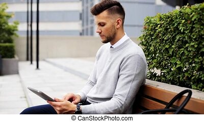 man with tablet pc sitting on city street bench - business,...