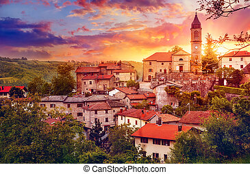 Sunset over old provincial town with Bell tower in Italy red...