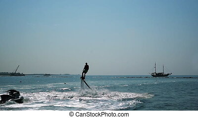 Silhouette of a Man Having Fun on Flyboard in the Sea -...