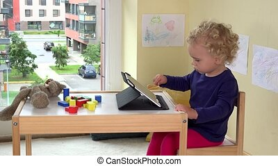 Emotional child using tablet computer. Poor teddy bear laying on table