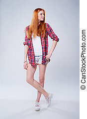 Full length beautiful red haired teen girl in plaid shirt...