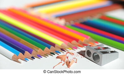 Color pencils and pencil sharpener on white paper
