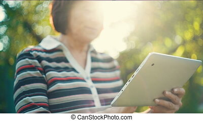 Aged Woman With Tablet PC - Aged woman working with tablet...