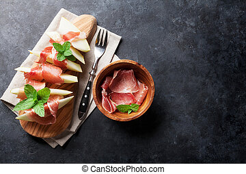 Fresh melon with prosciutto and mint. Antipasti. Top view on...