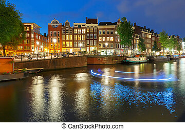 Night city view of Amsterdam canal with dutch houses -...