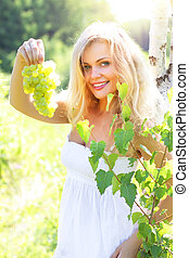 Beautiful girl holding grapes