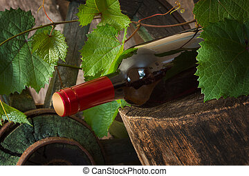 A bottle of wine on the background of the vine in a vintage...