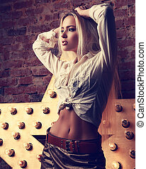 Sexy makeup blond woman posing in white shirt and skirt with...