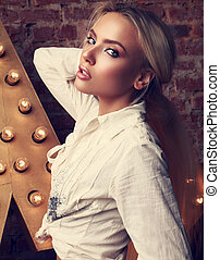 Sexy glamour blond woman posing in white shirt on yellow star and brickes background