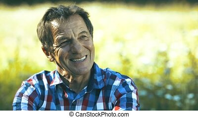 Senior man in checked shirt on sunny summer meadow. - Happy...