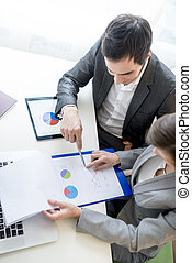 Two business partners analysing a report - Two business...