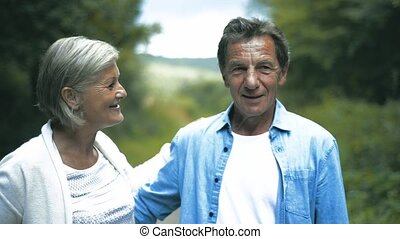 Beautiful senior couple on a walk on sunny summer day -...