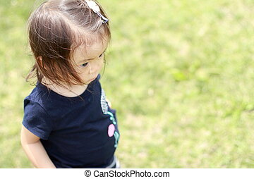 Japanese girl standing on the grass (1 year old)