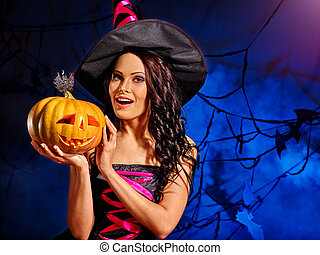 Witch keeps big orange Halloween pumpkin. - Happy witch...