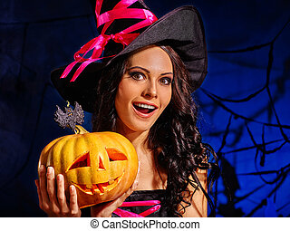 woman wearing witch hat holding big pumpkin. - Happy young...