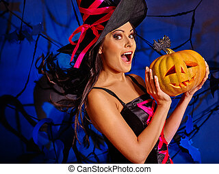 Woman wearing witch hat keeps big orange pumpkin. - Happy...