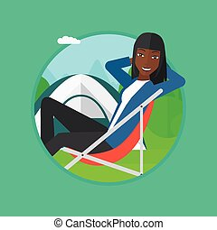 Woman sitting in folding chair in the camp. - An...